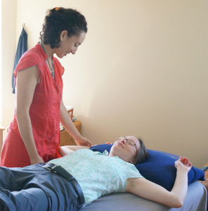Adrianna talking with Christy prior to beginning to poke her with nickel free acupuncture needles.