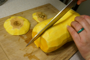I recommend using a sharp knife and large cutting board. Carefully cut the ends off the squash and slice it in half.