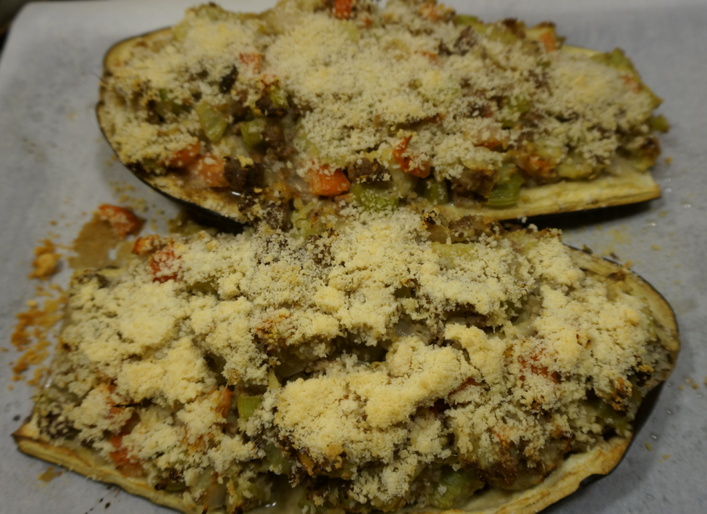 Cooked nickle free stuffed eggplant, with one with parmesan cheese on the bottom.