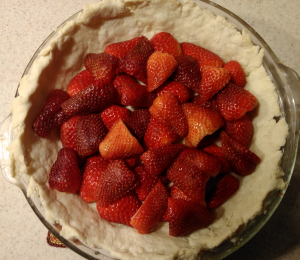 Place half of the cut strawberries in the cooked pie crust.