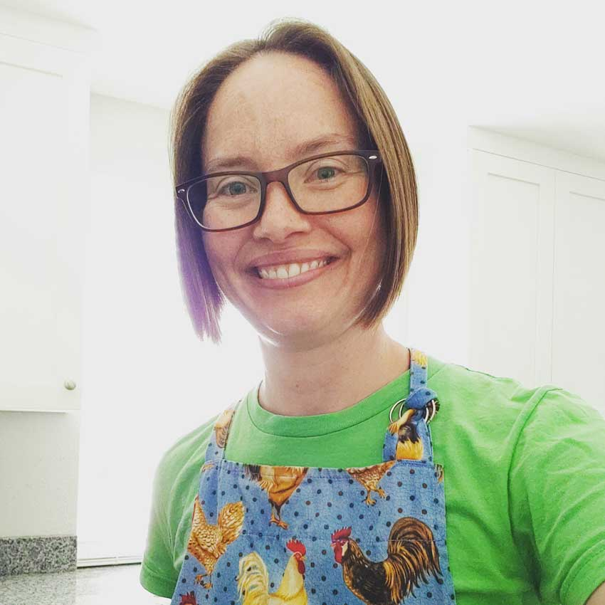 Profile picture of Christy Cushing in an apron in her kitchen.